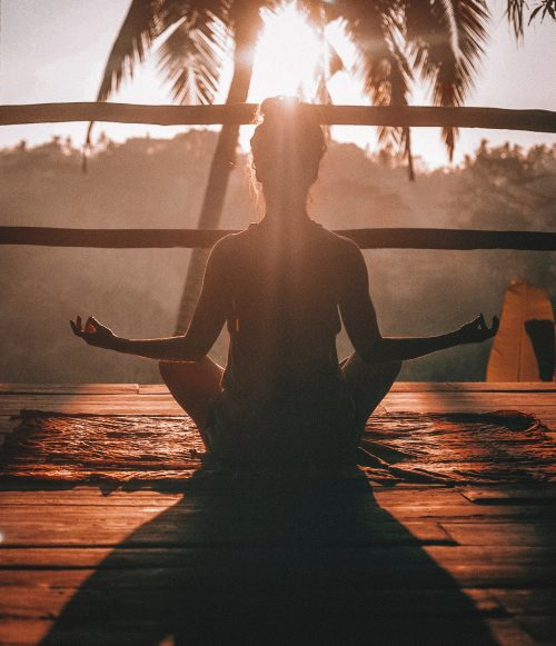 Image of woman doing her daily yoga practice in front of a tropical sunset